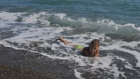 Boy in the sea surf. Child covers the wave. The boy lies in the sea on the rocks. Water lulls the baby. Boy fell asleep in the sea surf. Child covers the wave stock footage