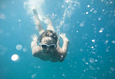 The boy in the sea swimming under water. The boy dived into the sea and swimming under water at the viewer Royalty Free Stock Photography