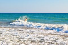 The boy in the sea wave surf. Kaifas beach, Greece Royalty Free Stock Photo