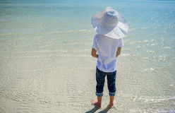 A boy at the sea. White t-shirt, dark trousers and hat. Barefoot on white sand and clear water. Rear view.  Stock Images