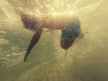 Boy swimming in sea. Young boy swimming or snorkeling in the sea with bubbles and sunshine Royalty Free Stock Image