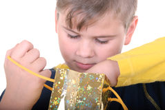 Boy searches for a gift in a bag. On a white background Stock Photo