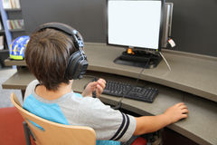 Boy searching internet. In the library Royalty Free Stock Images