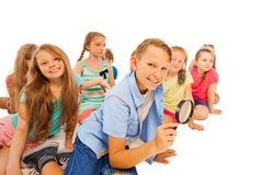 Boy searching with magnifying glass and friends Royalty Free Stock Photo