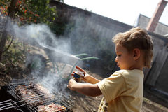 Boy seasoning pork chops with pepper Royalty Free Stock Images