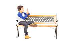 Boy seated on bench and playing cards with imaginary friend royalty free stock photography