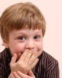 Boy With Secret. Young boy with mischievous expression wearing striped shirt Royalty Free Stock Images