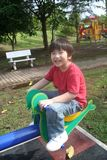 Boy on seesaw. Happy boy playing seesaw at the playground in the park Royalty Free Stock Photo