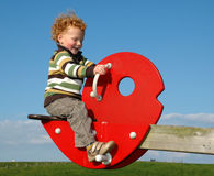 Boy on SeeSaw. Happy little Boy having fun on a seesaw, against a blue sky Royalty Free Stock Photos