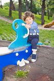Boy in seesaw looking away Royalty Free Stock Image