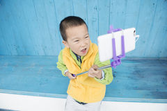 Boy self shot. Chinese boy self shot outdoor with smartphone Royalty Free Stock Image