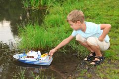 Boy sends toy ship in floating Royalty Free Stock Images