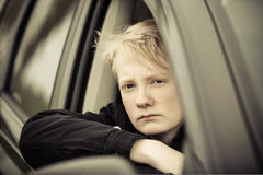Boy with serious expression and folded arms in car Stock Photo