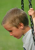 Boy Serious on Swing Royalty Free Stock Photos