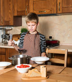Boy serving Borshch, traditional Russian and Ukrainian soup. Pouring soup into a plate with ladle from pan in kitchen. Royalty Free Stock Photo
