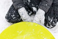 A boy of seven years old sitting on the snow and a green plastic saucer sled lying near him. Concept of winter activities,. Recreation and children`s stock photo