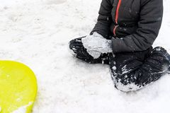 A boy of seven years old sitting on the snow and a green plastic saucer sled lying near him. Concept of winter activities,. Recreation and children`s royalty free stock images