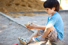 Boy shakes the sand out of the shoe. On the playground Stock Photo