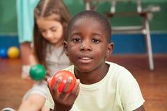Boy sharing a plastic ball Stock Image