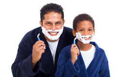 Boy shaving father. Playful little indian boy shaving with father isolated on white royalty free stock images