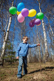 Boy with sheaf of balloons in park in spring stock images
