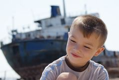 Boy and ship. Portrait of young boy with big old ship on background Stock Photo