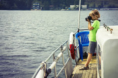 Boy on the ship photographing water Stock Photography