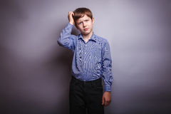 Boy shirt ponders over gray background. Boy in shirt ponders over gray background Royalty Free Stock Photography