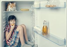 A boy in a shirt and shorts eating an apple inside a fridge with food and product. Close-up Royalty Free Stock Photography