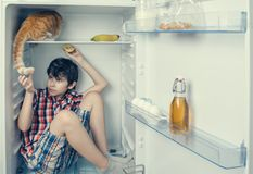 A boy in a shirt and shorts with red cat inside a fridge. A boy is going to take a cat tail royalty free stock photos