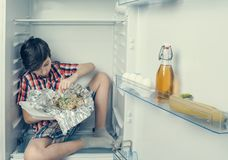 A boy in a shirt and shorts unwrapping a food package sitting in a refrigerator. Close-up. A boy in a shirt and shorts unwrapping a food package sitting in a Royalty Free Stock Photos