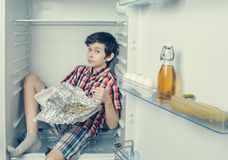 A boy in a shirt and shorts unwrapping a food package sitting in a refrigerator. Close-up. A boy in a shirt and shorts unwrapping a food package sitting in a Royalty Free Stock Images