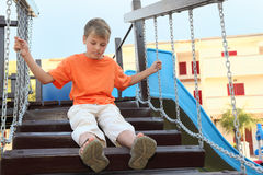 Boy in shirt sitting on suspension bridge Royalty Free Stock Images