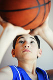 Boy Shooting Basketball. A young boy concentrating getting the basketball into the hoop. He is looking up at the ball stock images