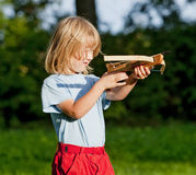Boy shooting with crossbow. Little boy with long blond hair shooting with toy crossbow in the garden Stock Photos