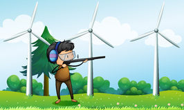 A boy shooting in front of the windmills Royalty Free Stock Images