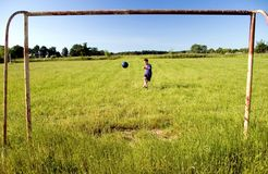 Boy shooting at goal. A boy practicing his football skills, shooting at empty goal, the ball in the mid air Royalty Free Stock Photo