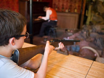 Boy Shooting Gun. A boy takes aim at an amusement park shooting gallery royalty free stock photos