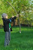 Boy shooting with a hand made bow and arrow. Archery Royalty Free Stock Photo