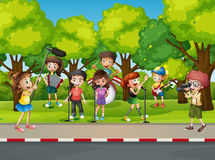 Boy shooting his friends singing in the park Royalty Free Stock Images