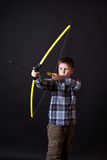 Boy shoots a bow. On a black background Royalty Free Stock Images