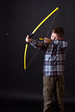 Boy shoots a bow. On a black background Royalty Free Stock Photos