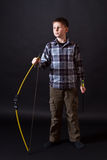 Boy shoots a bow. On a black background Stock Image