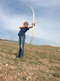 Boy shoots a bow at a target. In the open air Royalty Free Stock Photo