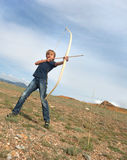 Boy shoots a bow at a target. In the open air Stock Image