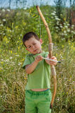 Boy shoots a bow. At a target, in the open air Royalty Free Stock Photos