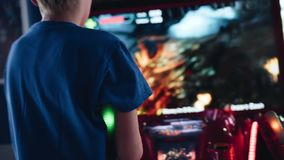 The boy shoots a flamethrower playing a video game in the arcade. View from behind. Children`s entertainment stock video