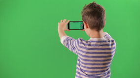 Boy shoots video on the smartphone. Green screen stock footage