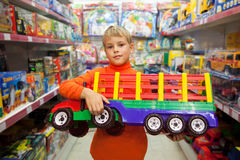 Boy in shop with big model of truck in hands Royalty Free Stock Photo