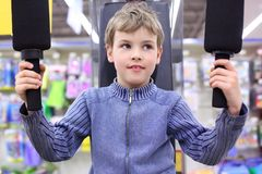Boy in shop on  sports exerciser Royalty Free Stock Photos